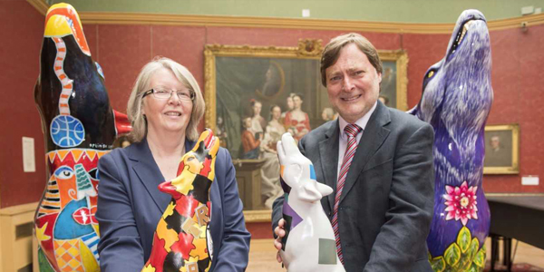 Cllr Claire Darke, Wolves in Wolves artist, and Cllr John Reynolds with two of the mini wolves